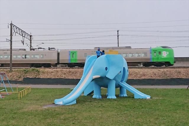 象の滑り台で遊ぶ子供と列車
